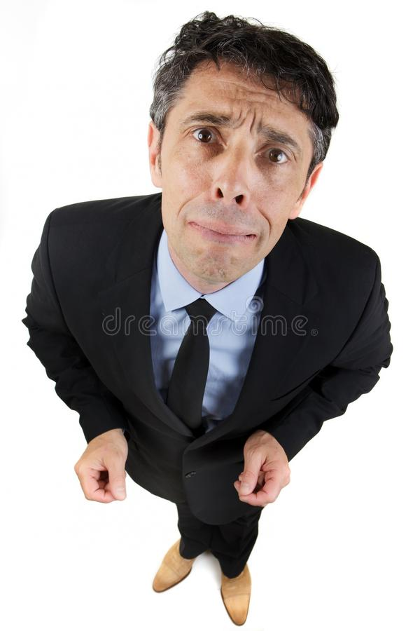 Upset sorrowful businessman. Standing looking up at the camera with a pitiful expression as though about to burst into tears, high angle fun portrait on white stock photo