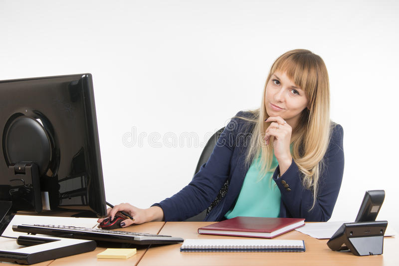 Upset by a specialist working in the office computer, look into the frame. Young woman secretary sitting at office desk working, isolated on white background royalty free stock images