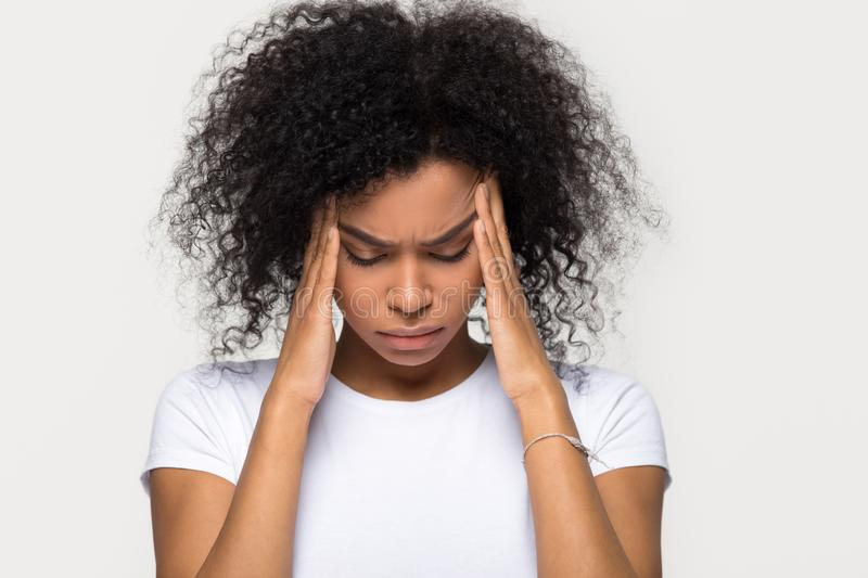 Upset stressed black woman massaging temples feeling pain terrible migraine. Sad tired sick african american girl suffering from strong headache concept stock images