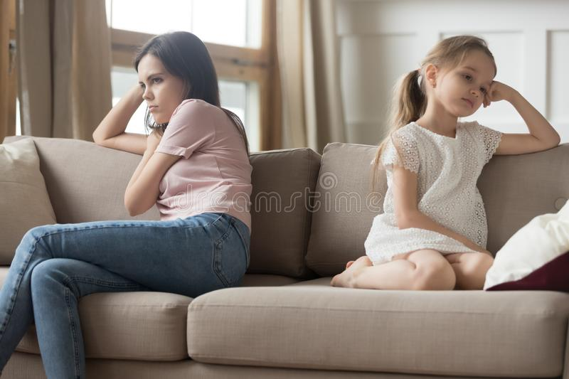 Stubborn mother and child girl sitting turned away on sofa. Upset stubborn mother sister and little child girl sitting back turned away on sofa not talking after stock image