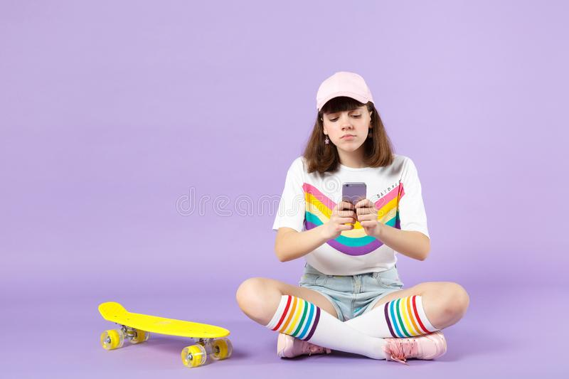 Upset teen girl in vivid clothes sitting near skateboard, using mobile phone, typing sms message isolated on violet stock photos