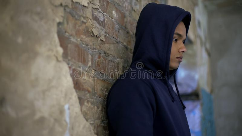 Upset teenage boy in house destroyed by war, suffering poverty, depression. Stock photo royalty free stock photography