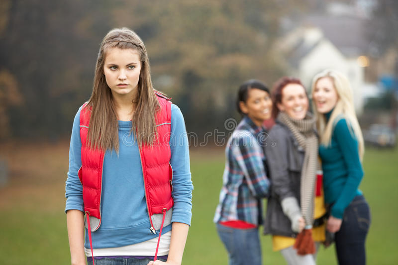 Upset Teenage Girl With Friends Gossiping. In Background in park royalty free stock photo