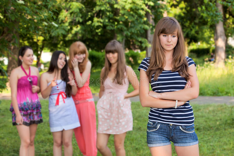 Upset teenage girl with friends gossiping. In park royalty free stock photos