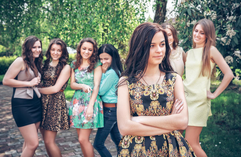 Upset teenage girl with friends gossiping. In park stock photography