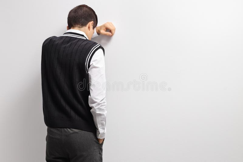 Upset teenage student with his head against a wall stock photography