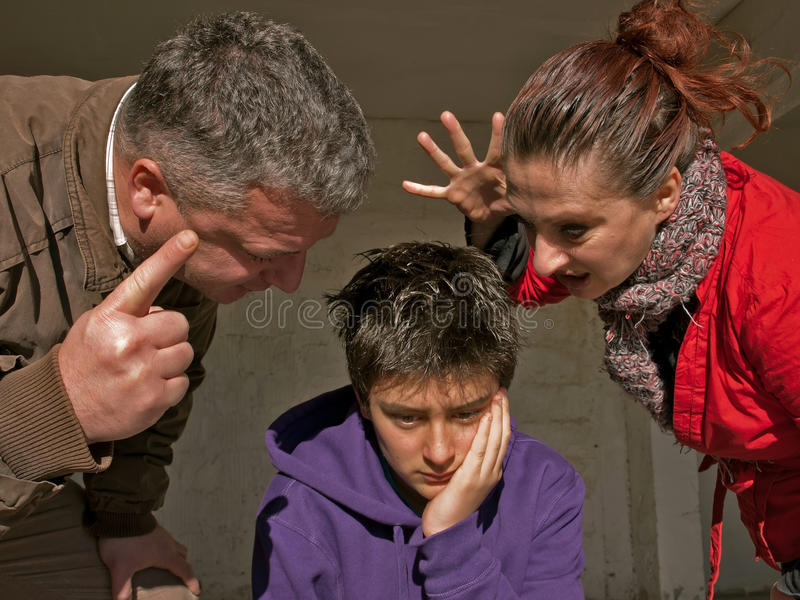 Upset teenager and family. Mother and father raise the noise and clamor, threatening, gesturing toward a troubled teenage during emotional crisis. Teenager is a