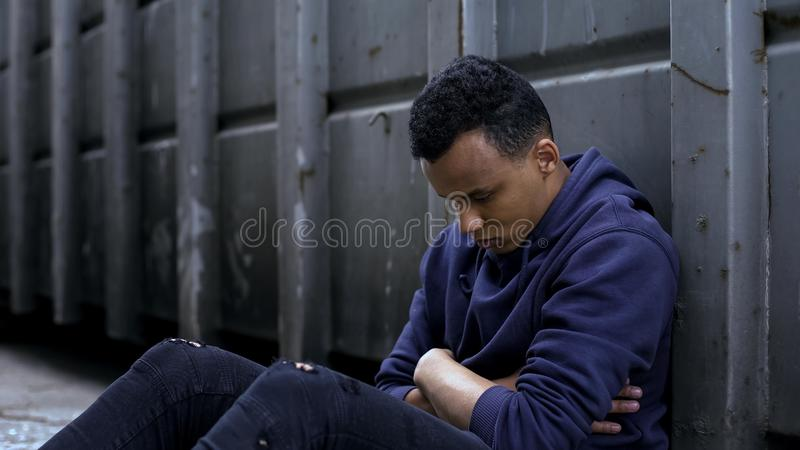 Upset teenager sitting in gateway, emigrant facing life difficulties, homeless stock images