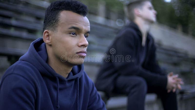 Upset teenagers sitting on stadium tribune, watching sports game of youth team. Stock photo stock images