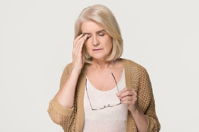 Tired old woman holding glasses feeling eyestrain on background stock images