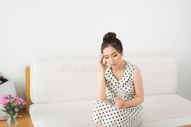 Upset Vietnamese woman on couch at home in the living room stock photography
