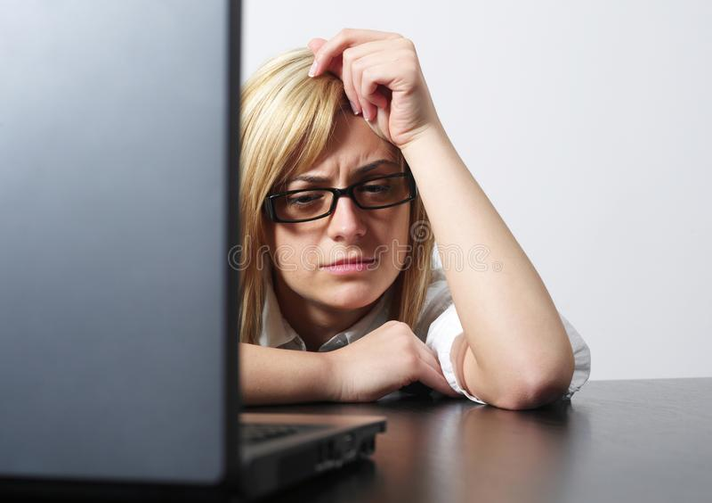 Upset woman at desk. Upset women looking at laptop stock photography