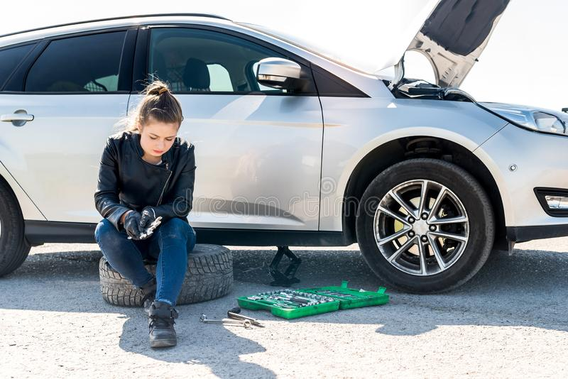 Upset woman with different wrenches and broken car royalty free stock images