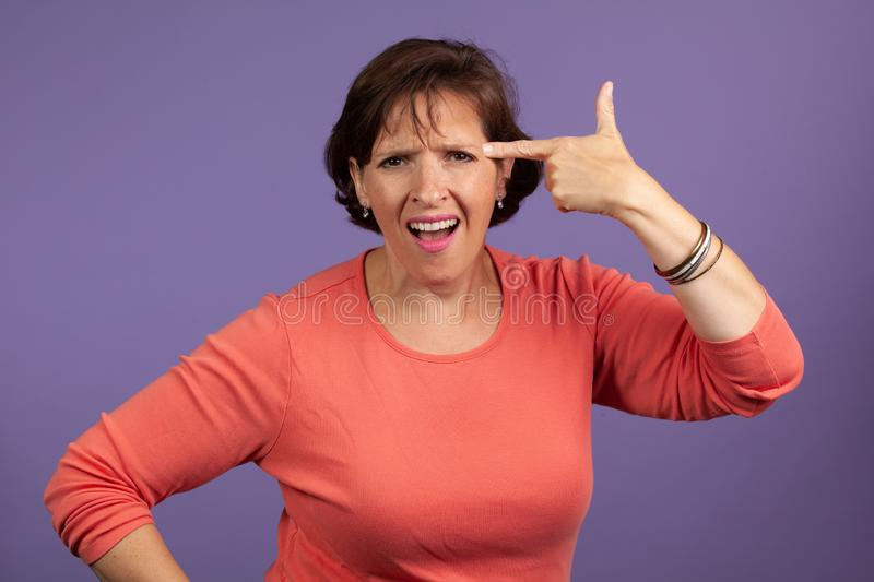 Upset woman with finger to head. Mature woman in studio with finger to head. Argument angry concept image royalty free stock photography