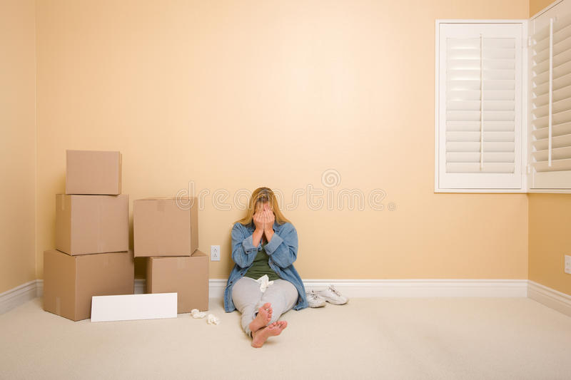 Upset Woman on Floor Next to Boxes and Blank Sign. Upset Woman with Tissues on Floor Next to Boxes and Blank Sign in Empty Room stock photo