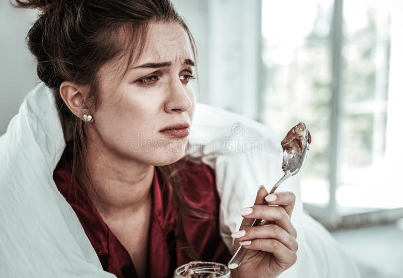 Upset woman holding a spoon of dessert royalty free stock image