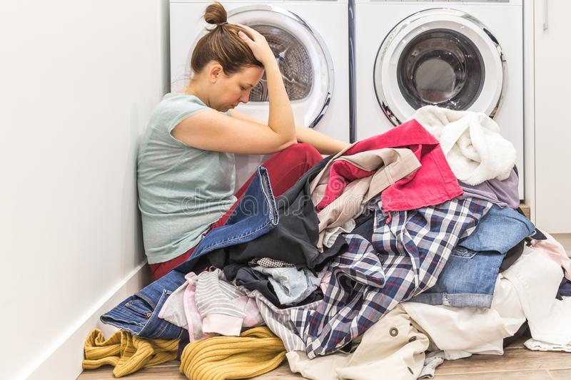 Upset woman in laudry room sitting ona floor with dirty clothes royalty free stock photos