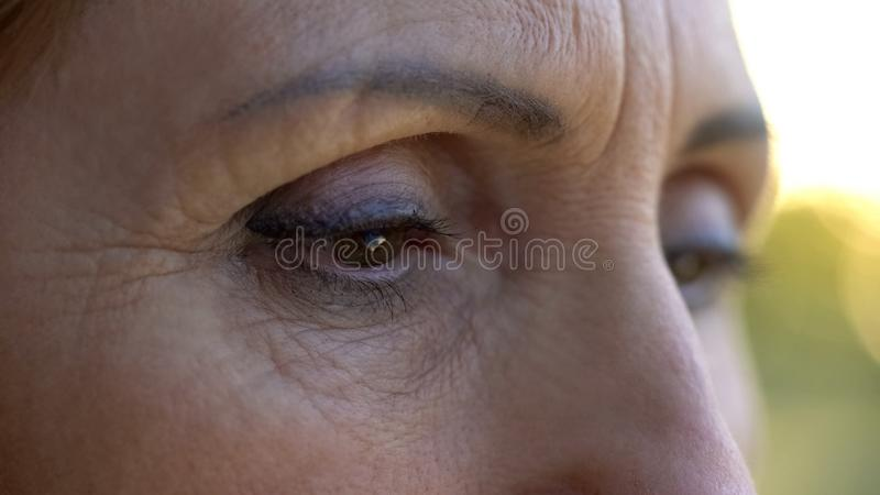 Upset woman looking down, regretting wrong decisions, ashamed, eyes close up stock image