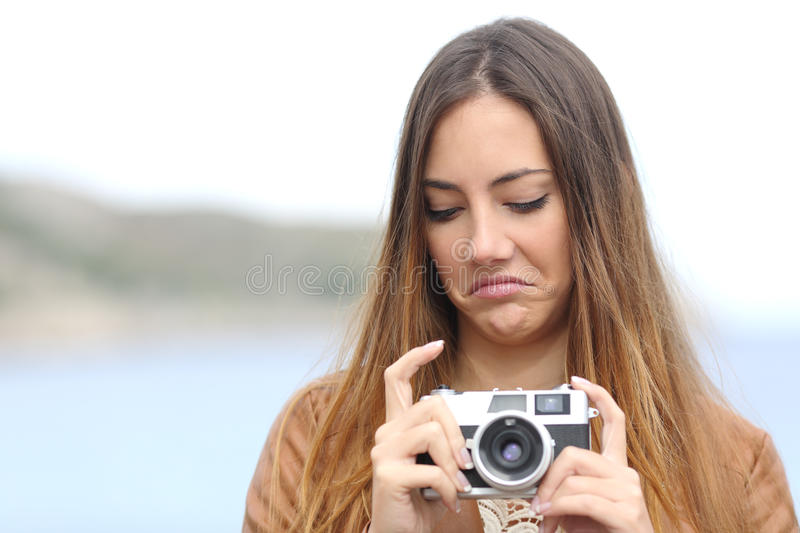 Upset woman looking her old slr photo camera stock photography