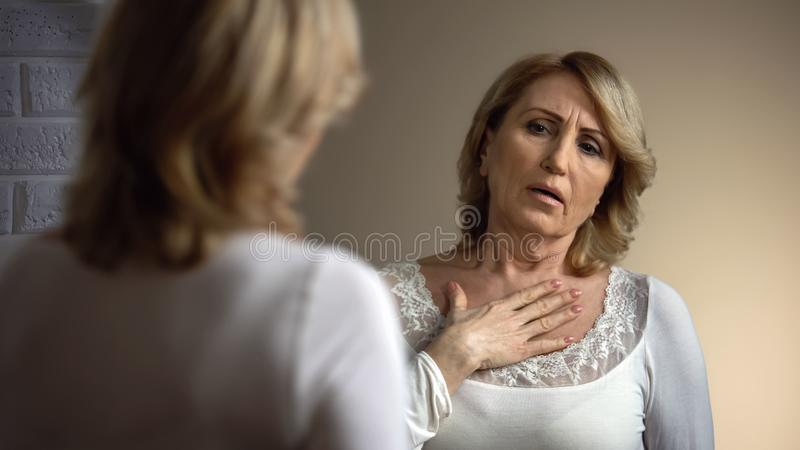 Upset woman looking in mirror and hardly breathing, health problems, heart pain stock photos