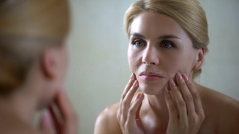 Upset woman looking in mirror and touching face, sad about skin aging, wrinkles stock photography