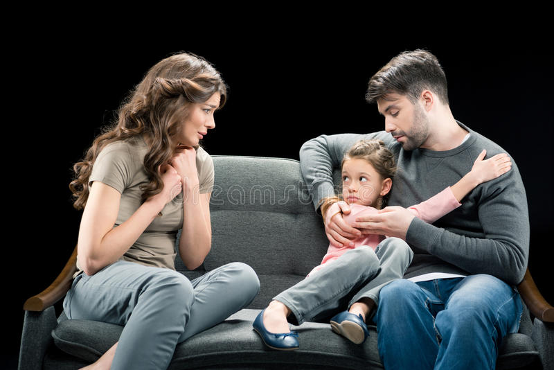Upset woman looking at scared daughter hugging with father stock images