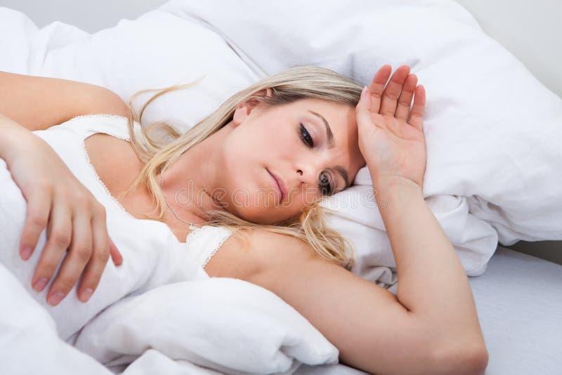 Upset woman lying on bed stock photo
