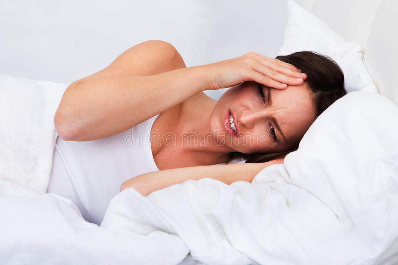 Upset woman lying on bed royalty free stock photo