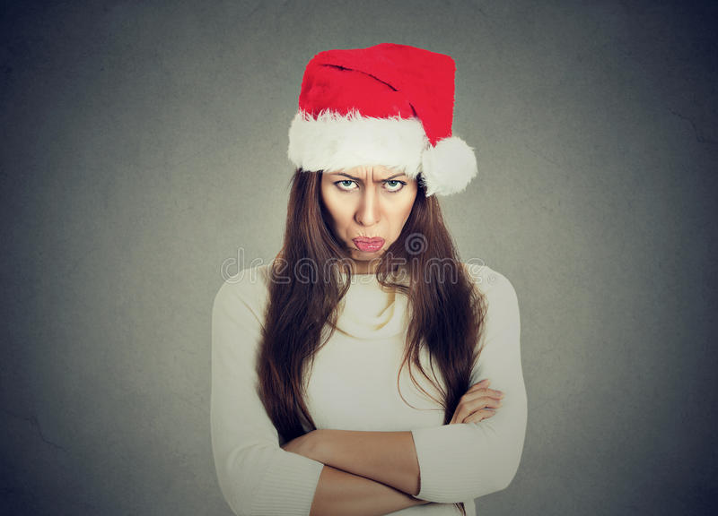 Upset woman in santa claus hat arms crossed looking at you royalty free stock photos
