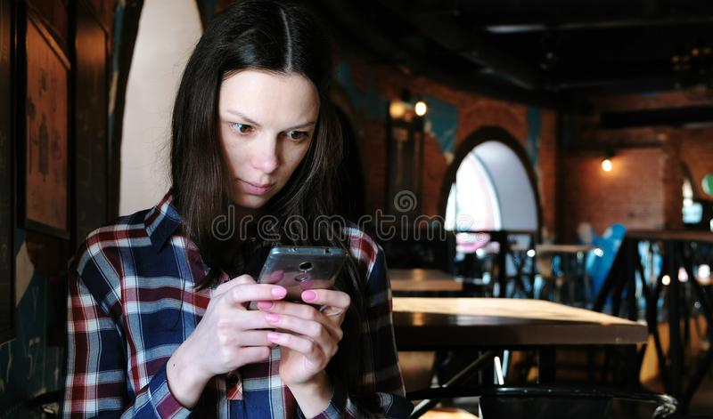 Upset woman sends a message or use internet in the phone sitting in a cafe. Dressed in a plaid shirt. Upset woman sends a message or use internet in the phone royalty free stock image