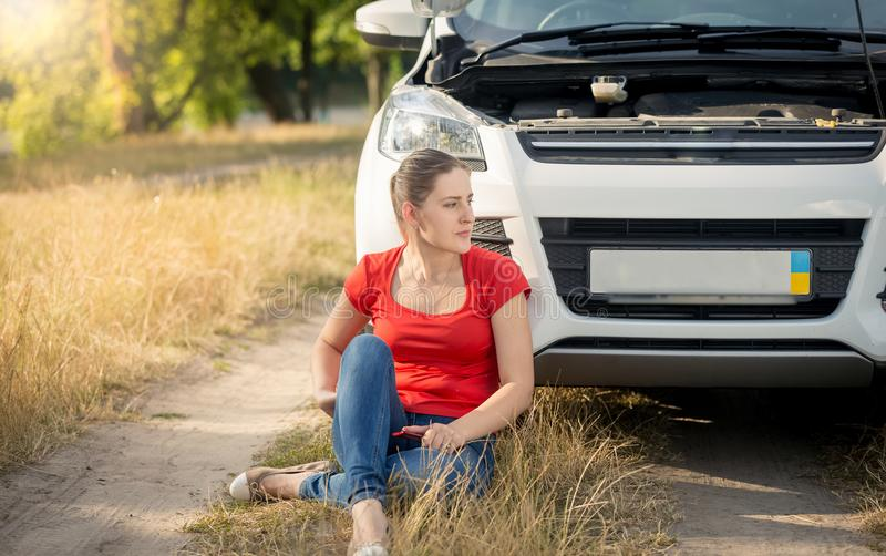 Upset young woman sitting on ground and leaning on her broken car on countryside road stock images