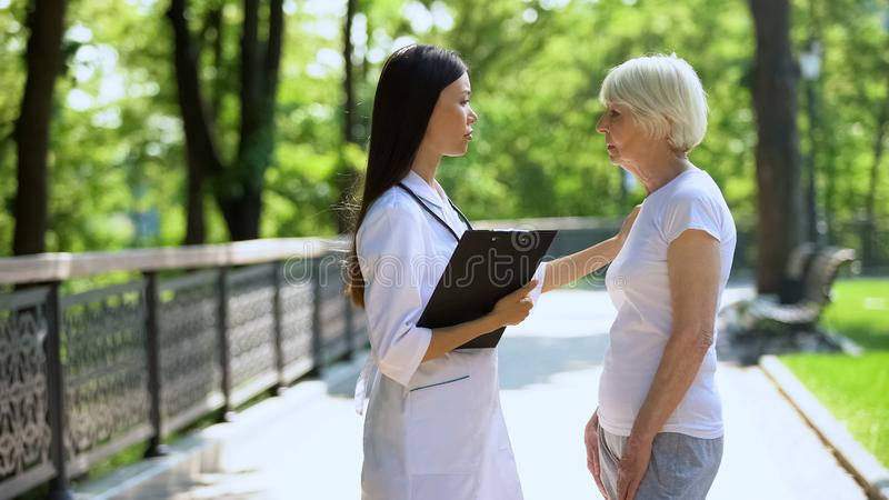 Upset woman talking with doctor in medical clinic park, fatal disease concept. Upset women talking with doctor in medical clinic park, fatal disease concept royalty free stock photo