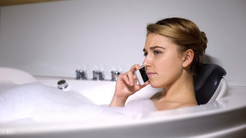 Upset woman talking phone in bath with foam bubbles, negative news, close-up royalty free stock image