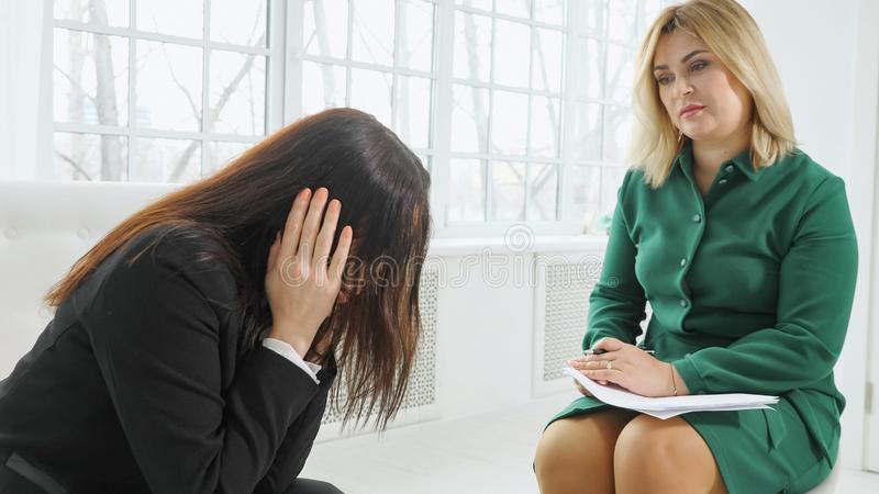 Upset woman having consultation with female psychologist royalty free stock photo