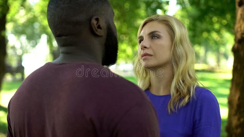 Upset woman sadly looking at boyfriend, relationship crisis, interracial love royalty free stock photo