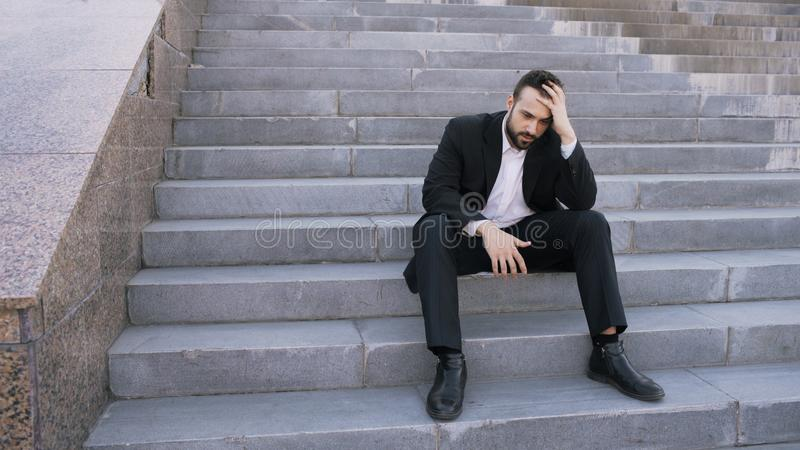 Upset young business man having stress and sitting on stairs in street. Businessman having deal problems concept royalty free stock photography