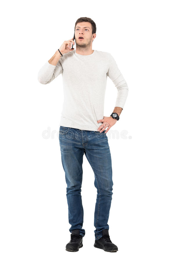 Upset young casual man arguing on the mobile phone. Full body length portrait isolated over white studio background royalty free stock photography