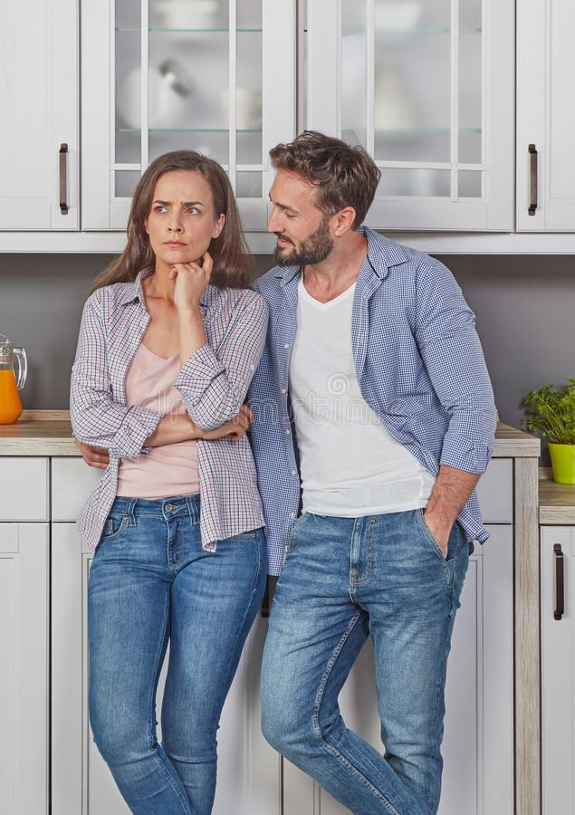Relationship difficulties concept. Upset young couple in the kitchen stock image