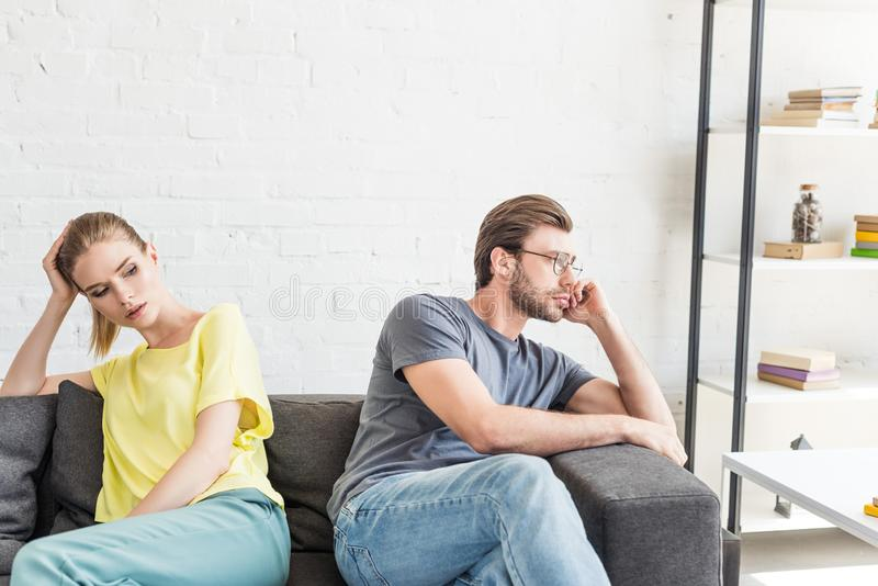 upset young couple sitting separated on sofa royalty free stock images