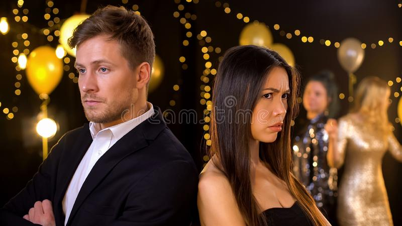 Upset young couple standing turned away in night club, relationship conflict royalty free stock photography