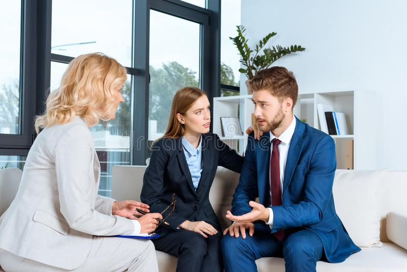 upset young couple talking with psychologist stock photography