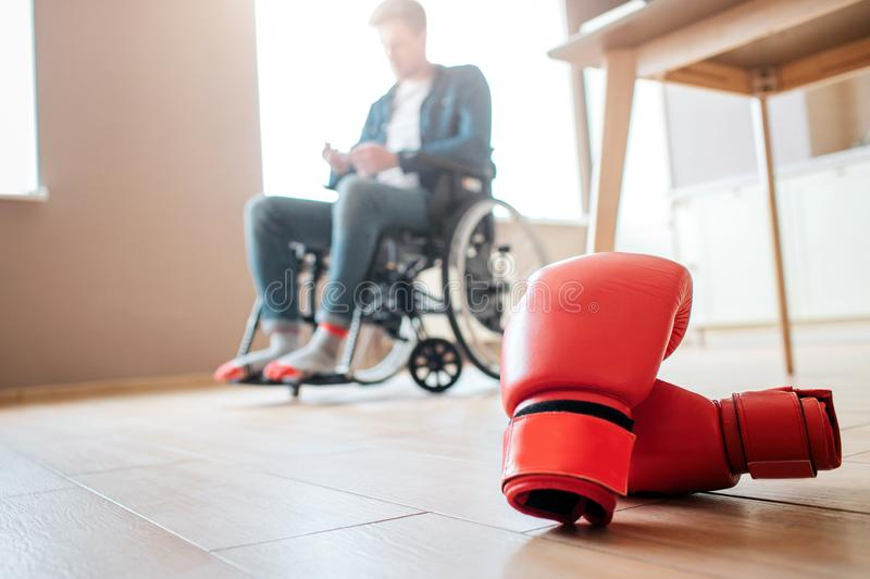 Upset young ex-sportsman with disability and inclusiveness sitting on wheelchair. Boxer`s gloves lying on floor. Can`t royalty free stock photos