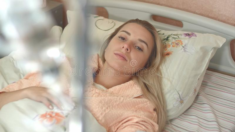 Upset young female patient looks at IV drip stand. Close up. Professional shot in 4K resolution. 102. You can use it e.g. in your commercial video, business royalty free stock photography