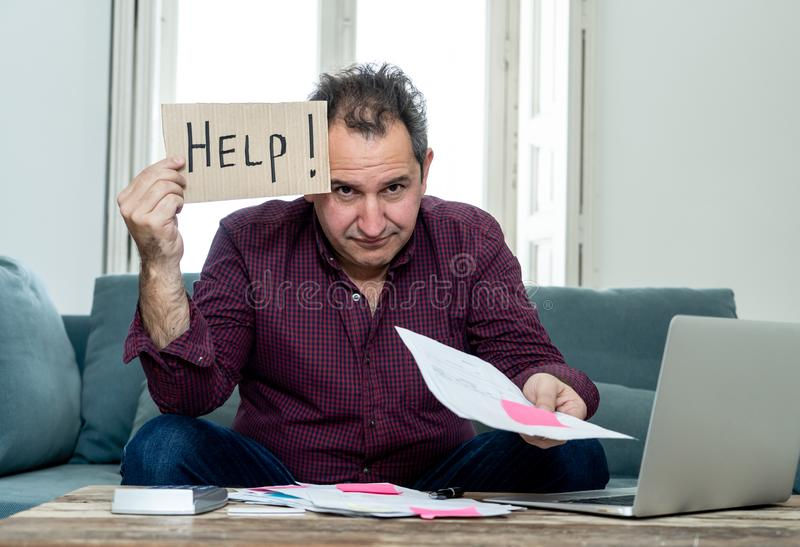 Upset young man asking for help in paying bills Mortgage home or business finance problems. Worried and desperate mature man asking for help in paying off debts royalty free stock photography