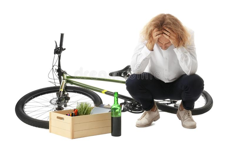 Upset young man with bottle of wine and box of belongings near bicycle royalty free stock images