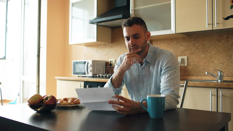Upset young man reading letter with unpaid bill in the kitchen at home royalty free stock image