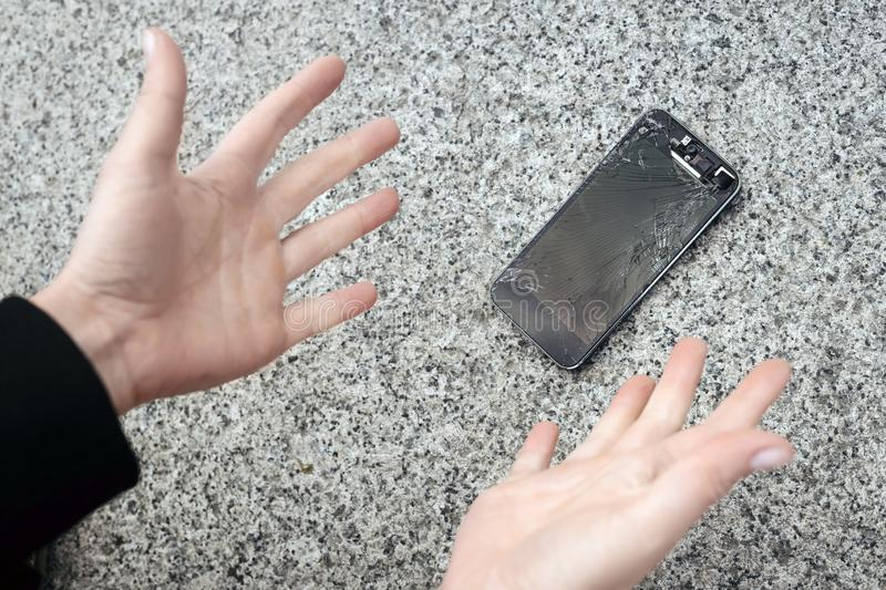 Upset young man sits and holds a broken smartphone with a cracked glass screen. Copy space royalty free stock photo