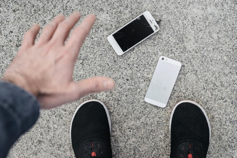 Upset young man sits and holds a broken smartphone with a cracked glass screen. Copy space stock photography