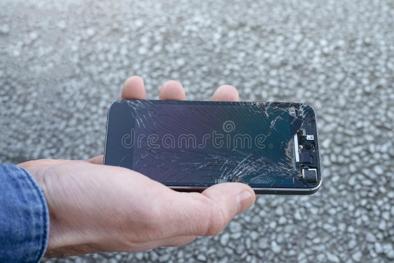 Upset young man sits and holds a broken smartphone with a cracked glass screen. Copy space royalty free stock photos
