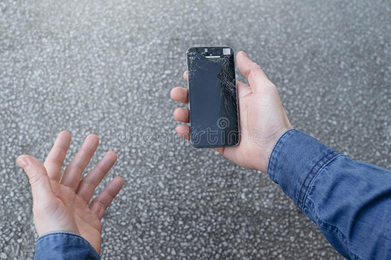 Upset young man sits and holds a broken smartphone with a cracked glass screen. Copy space royalty free stock images